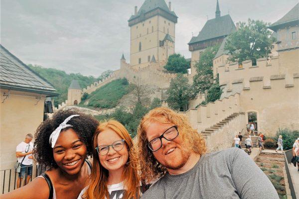 3 TEFL trainees standing in front of Karlštejn castle