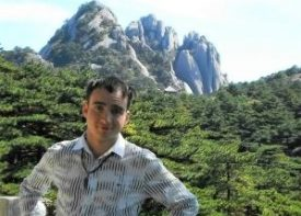 TEFL graduate stood in front of tree covered mountains