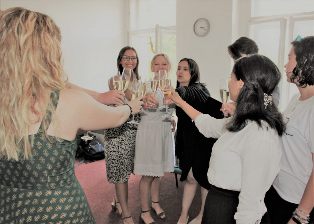 Group of TEFL trainees clinking champagne glasses at graduation party