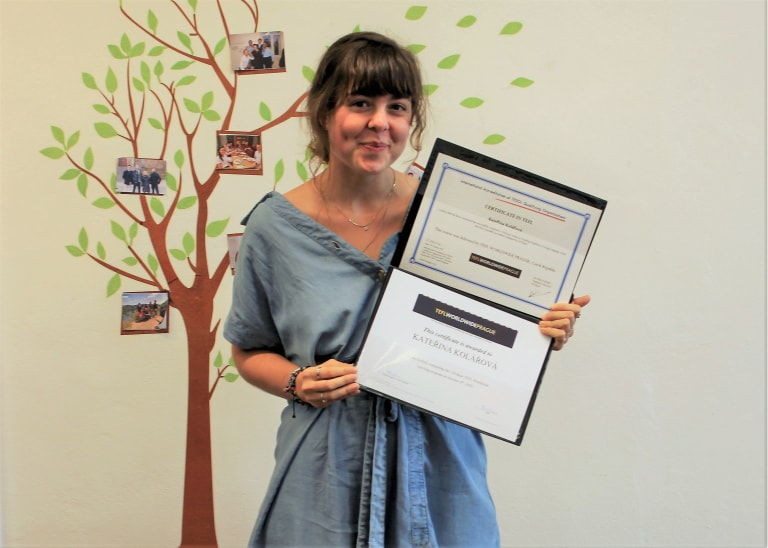 TEFL graduate holding up certificate at graduation party