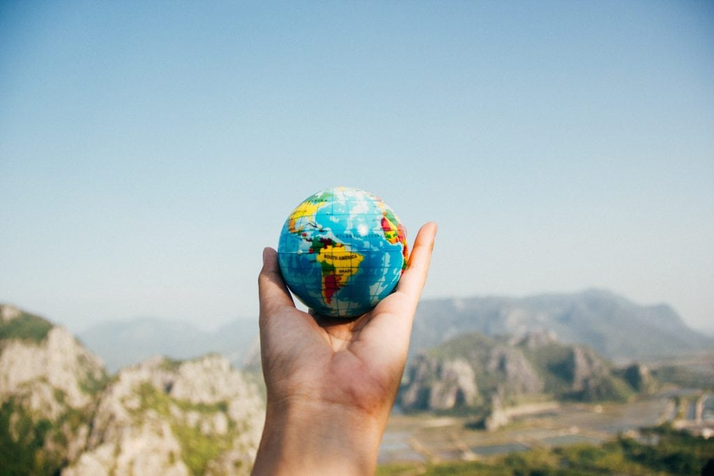 Hand holding up a small globe with rocks and mountains in the background