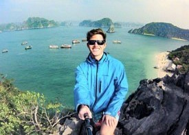 TEFL graduate holding up camera on top of cliff with exotic sea and islands behind him