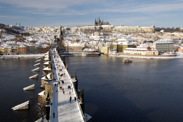 Charles bridge in the foreground with Prague castle in the background. Covered in snow in the winter
